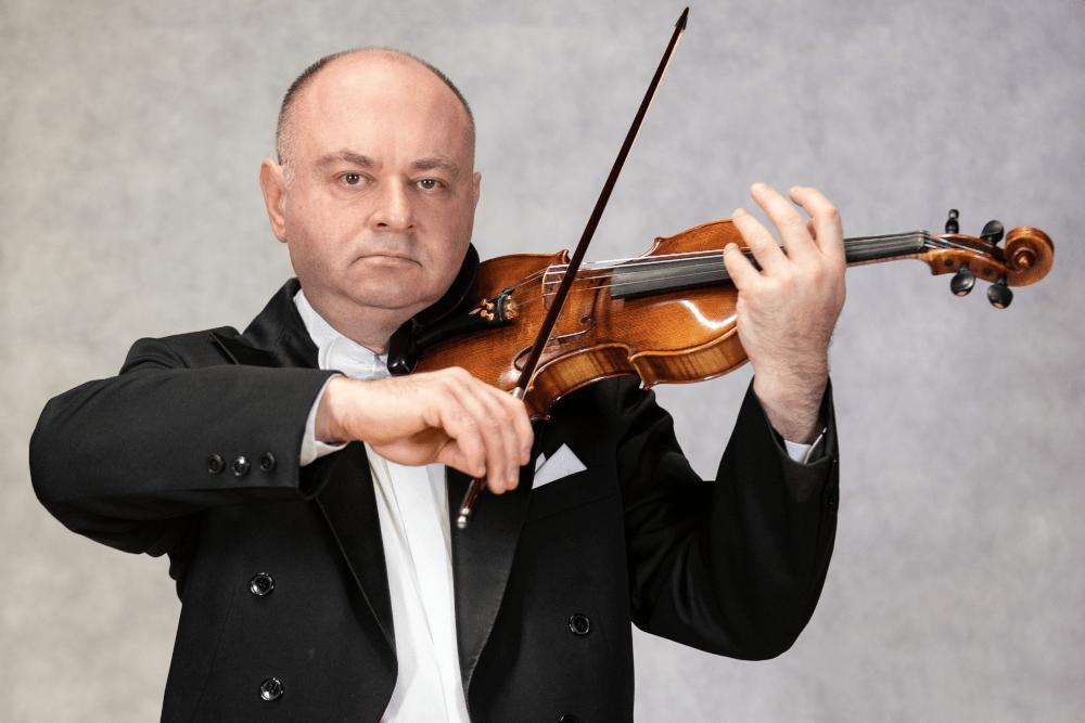 Zdjęcie Grzegorza Cholewińskiego pozującego grę na skrzypcach