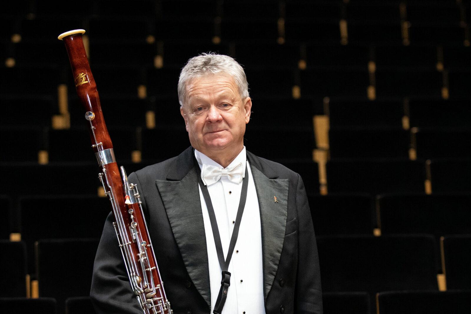 Zdjęcie Wiesława Kapronia z fagotem na tle miejsc na sali koncertowej