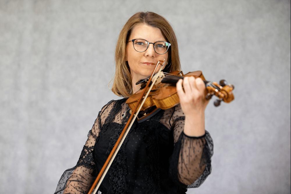 Zdjęcie Aleksandry Mazurek pozującej ze skrzypcami, po których ciągnie smyczkiem po strunach