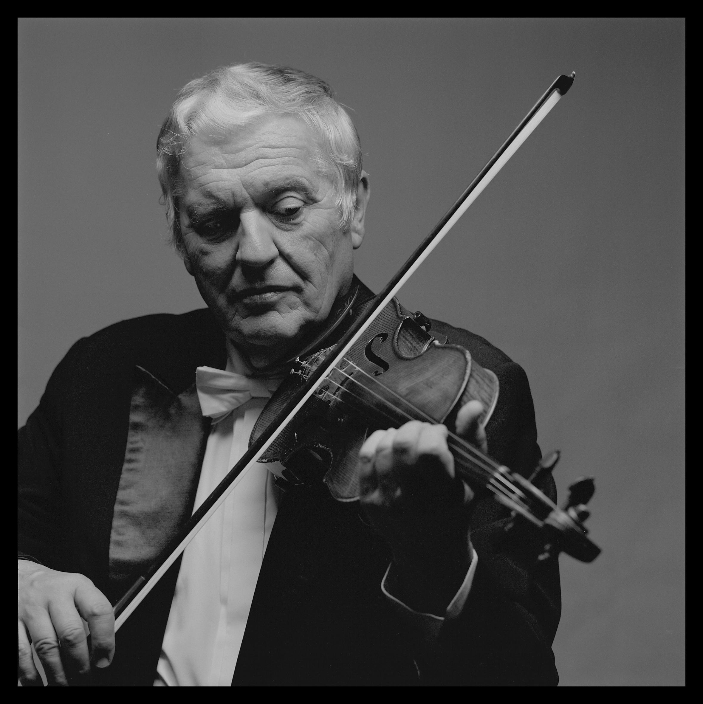 Konstanty Andrzej Kulka we fraku grający na skrzypcach. Czarno-białe