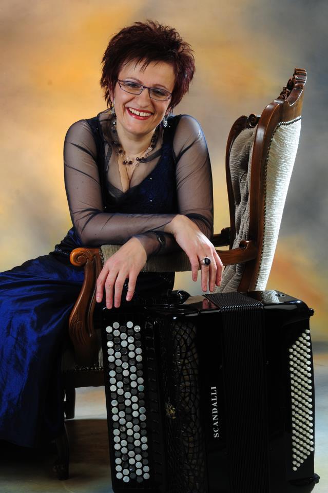 Artystka siedzi na krześle i opiera się o akordeon