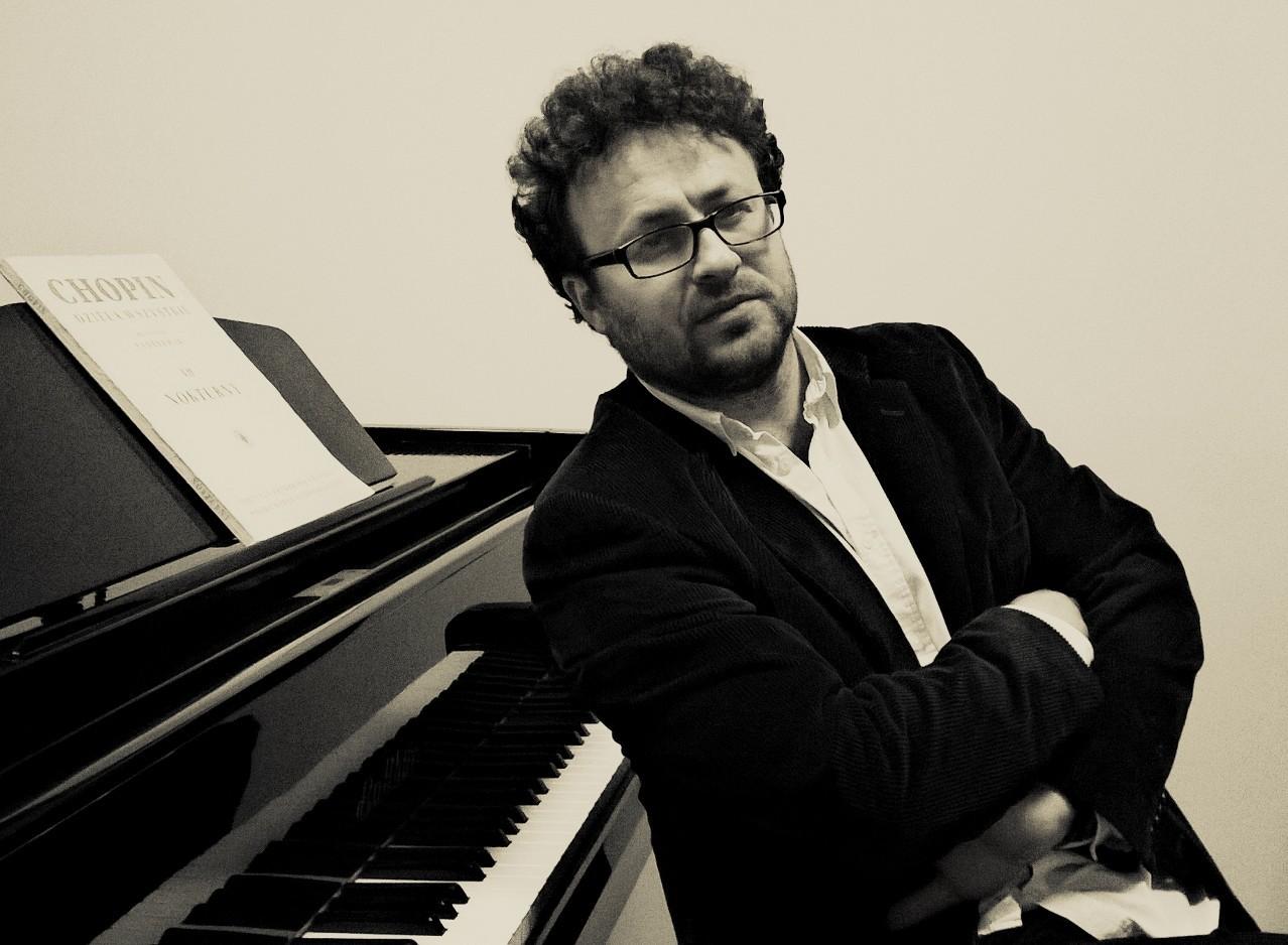 Artysta oparty o klawiaturę fortepianu. Ma założone ręce