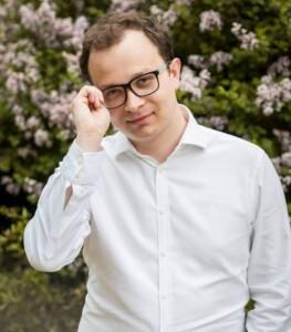 Mężczyzna w białej koszuli trzyma się jedną ręką za okulary